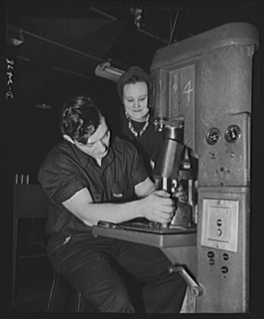 Women in defense. This Middlewestern plant has converted not only its machinery but also its skilled labor force from the peacetime production of electric fans and motors to the war production of twenty-millimeter shell boosters. Here a veteran employee of the plant's experimental division teaches a former farmerette the operation of a Haskins drilling machine, which drill holes in a twenty-millimeter shell booster part