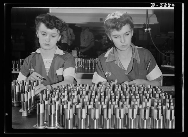 """Women in industry. Aircraft motor workers. It there's the slightest flaw in any of these airplane motor parts, it will be caught by Gabrielle Corveau (left) and Elizabeth Kamerer, two youthful inspectors employed by a Midwest aircraft motor plant. An erstwhile office worker, model and salesgirl, nineteen-year-old Miss Corveau has done war work for only a short while, but her work is on a par with the company's veteran employees. Mrs. Kamerer, twenty-four, sole supporter of herself and her invalid husband, finds her war job both interesting and exciting. """"It's thrilling to be a war worker,"""" she says"""