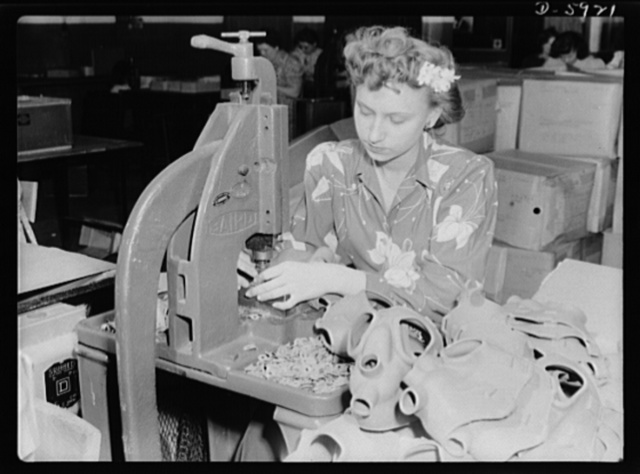 """Women in industry. Gas mask production. Flower in hair, Betty Gumbetter adds glamour to the assembly line of a Midwest gas mask factory which formerly made vacuum cleaners. Operating a riveting press, which attaches cloth tabs to the face pieces of gas masks, this young worker is one of the many company employees who switched over from work on vacuums when the plant was converted. Betty likes her new job better than the old one. """"It bears a lot more relationship to my American Women's Voluntary Services work,"""" she says. Eureka Vacuum, Detroit, Michigan"""