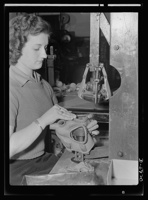 Women in industry. Gas mask production. Formerly a beauty shop operator, blonde Marjorie Karwaske finds that the dear dead days of bobby pins and curler clamps have left her with skillful, speedy fingers and a natural tendency to eliminate wasteful hand movement. These are invaluable aids to her job at a Midwest vacuum cleaner plant which has been converted to the production of gas masks. Those skillful fingers fasten eye pieces to the bodies of gas masks. Eureka Vacuum, Detroit, Michigan