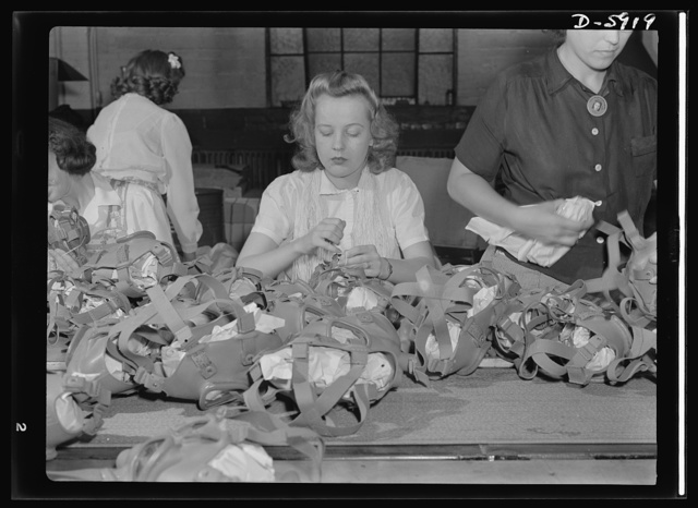 Women in industry. Gas mask production. Lacing head harnesses of gas masks after they have passed through all the stages of assembly and made ready for packaging, is the job of this young woman who works in a large Midwest vacuum cleaner factory which has been converted to war production. Note the lei of string she's wearing--the better to lace the masks with! Eureka Vacuum, Detroit, Michigan