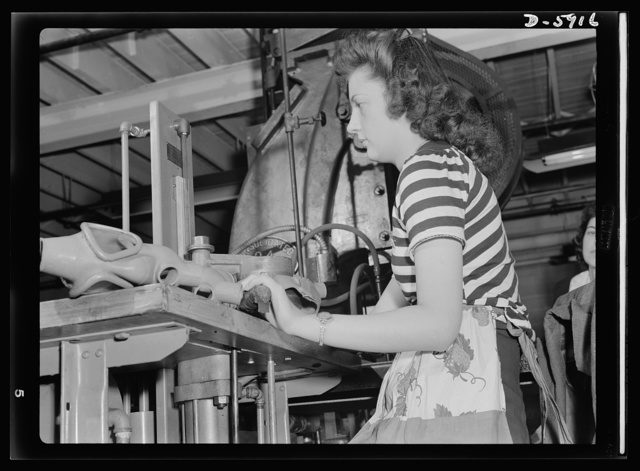 """Women in industry. Gas mask production. She used to wrap bread in a bakery, before Pearl Harbor, but today twenty-one-year-old Eugenia Bireta is a qualified government inspector who tests gas masks for """"eye leakage"""" on this pressure gauge. She's one of many young women employed by a large Midwest vacuum cleaner company now converted to production of gas masks. Eureka Vacuum, Detroit, Michigan"""
