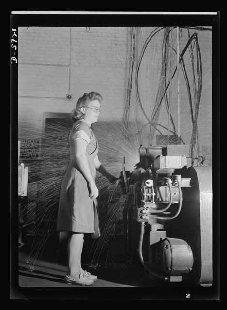 Women in industry. Tool  production. Eyes averted from the white shower of sparks, this young employee of a drill and tool plant touches the button that welds drills to their shanks. She's one of nearly 1,000 women who have replaced men at the production machines of this Midwest factory. Republic Drill and Tool Company, Chicago, Illinois