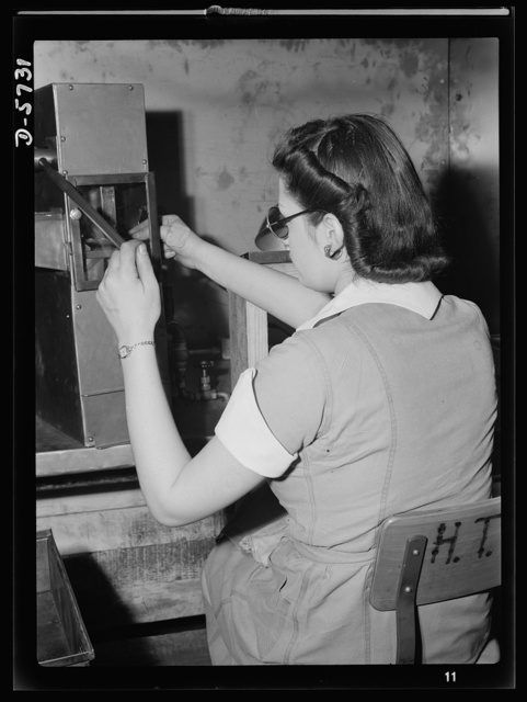 """Women in industry. Tool  production. Testing small diameter, high-speed twist drills, this young woman employed by a Midwest drill and tool company is one of America's women """"behind the men behind the guns."""" Drills must be perfectly made so that the nation's war weapons can be built to accurate specifications. Republic Drill and Tool Company, Chicago, Illinois"""
