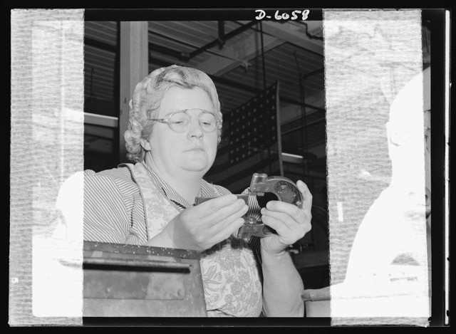 Women in war. Machine gun production. Intent on the important job at hand, Elsie M. Terry uses a precision snap gauge on the machine gun part she has milled. One of 2,000 women employed by a Midwest plant, converted from spark plugs to machine gun manufacture, Mrs. Terry typified the American woman war worker. Serious, skilled and reliable, she is making an invaluable contribution to the war effort. A.C. Spark Plugs