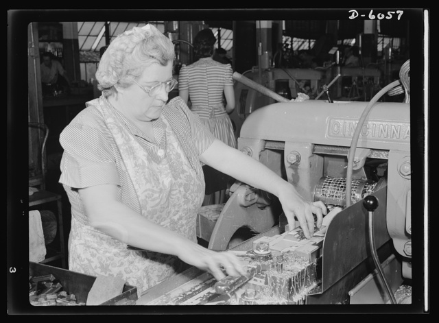 Women in war. Machine gun production operators. A woman's place is on the production line in this Midwest plant which has been converted from the manufacture of spark plugs to machine guns. Elsie M. Terry, one of 2,000 women employed here, is a skilled milling-machine operator who is making an important contribution to the war effort. She's making guns for America's armed forces. A.C. Spark Plugs