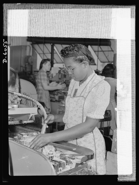 Women in war. Machine gun production operators. One of 2,000 women currently employed in a Midwest war plant, this young Negro worker has proven a competent and earnest machine operator. She processes gun parts in this plant which has been converted from the production of spark plugs to machine guns. A.C. Spark Plugs