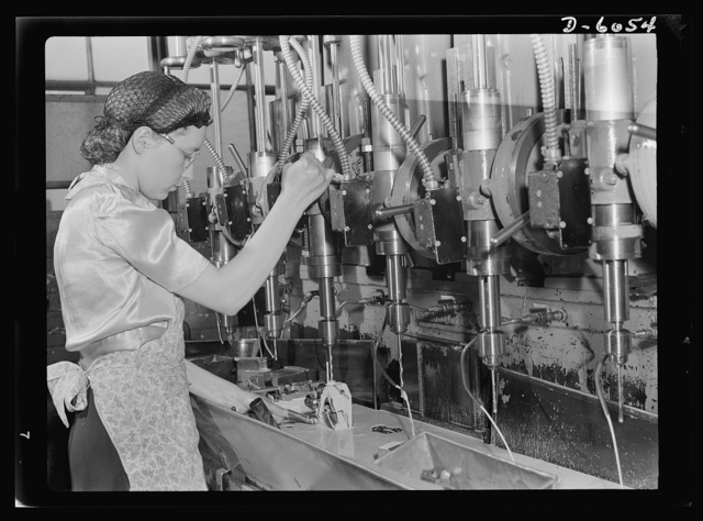 Women in war. Machine gun production operators. Operating a multiple drill press with speed and accuracy, this young woman is taking an active and important part in the war effort. She's machining gun parts in a Midwest plant which has shifted from production of spark plugs to the manufacture of machine guns on a full-time war basis. A.C. Spark Plugs