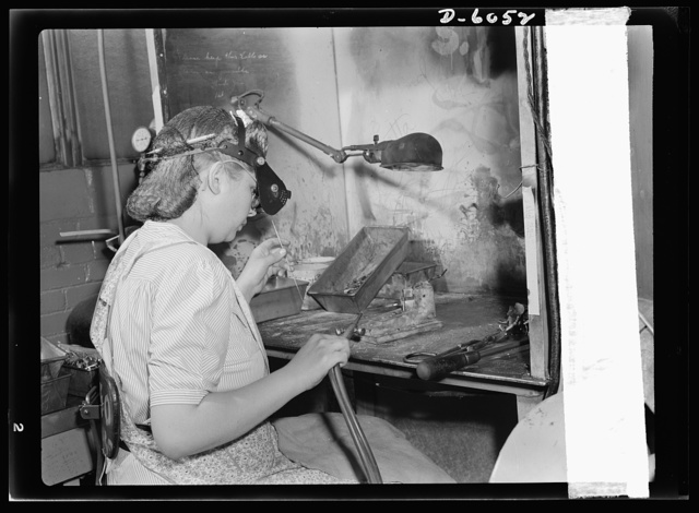 Women in war. Machine gun production operators. She carries a torch for the men of America's armed forces! Blonde, twenty-one-year-old Elne Nigholm brazes bolt latch releases for the Army's machine guns in a Midwest plant which has been converted from the manufacture of spark plugs to production of war materials. Two thousand women now work in this plant, with more to be added as production increases. A.C. Spark Plugs