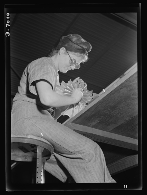 Women in war. Supercharger plant workers. Emily Sauermilch, baker, has taken her place in America's army of war workers. Employed in a large Midwest supercharger plant, she puts the finishing touches on impellors part of the airplane motor. Allis Manufacture Company
