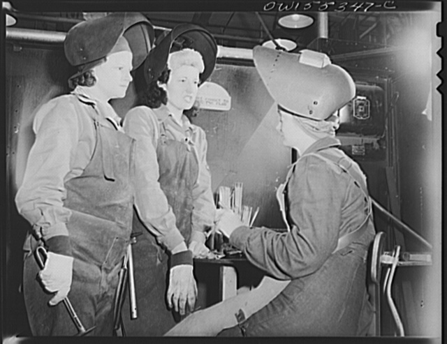 Women who are welders discuss the production of motor mounts and welded parts in their department