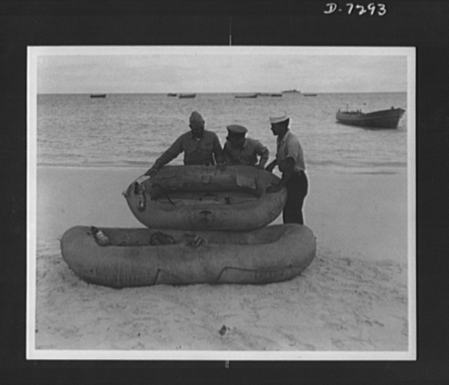 """Workers on Rickenbacker rescue boat. How mileage rationing can save lives on the battlefronts was pointed up dramatically by Captain Eddie Rickenbacker, who with six members of his crew were rescued after three weeks adrift on life rafts in the Pacific. """"One tire that is not wasted on pleasure driving may save the lives of seven men as ours was saved,"""" Rickenbacker said. One old rubber tire is sufficient to make a three-man raft of the type that saved the party in the Pacific"""