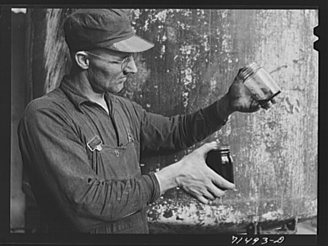 "Workman with samples of ""soap"" oil made from olives. The ""soap"" oil is a thick, dark green oil. Strathmore, California"