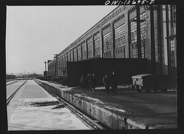 Workmen coming out of locomotive shops at the end of the shift at 40th Street shops, Chicago and Northwestern Railroad