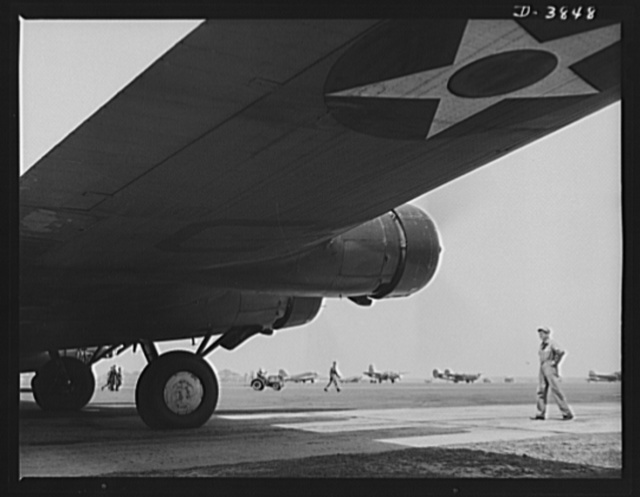 YB-17 bombardment squadron, Langley Field, Virginia. A warship of the air, a YB-17 bomber, poised for a takeoff at Langley Field, Virginia. A master sergeant of the bombardment squadron runs a practical eye over the big four-engine ship as the pilot warms up the engine