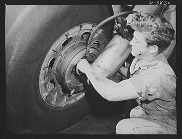 YB-17 bombardment squadron, Langley Field, Virginia. Brakes on the landing gear of a YB-17 bomber. A sergeant of a bombardment squadron at Langley Field, Virginia makes adjustments that will help this big warship  of the air to land smoothly
