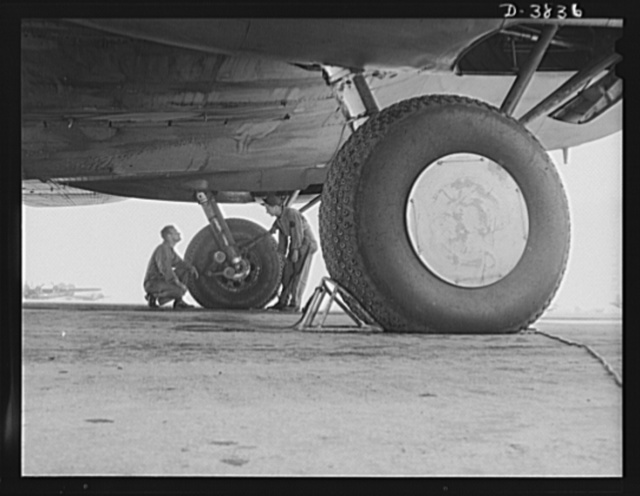 YB-17 bombardment squadron, Langley Field, Virginia. The enormous size of the landing wheels of a YB-17 bomber can be appreciated when compared with the sizes of the two men inspecting the landing gear. The men, a staff sergeant and a technical sergeant, belong to a bombardment squadron at Langley Field, Virginia
