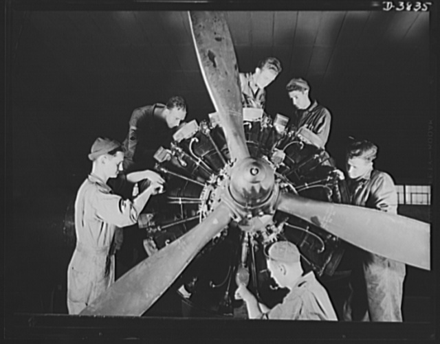 """YB-17 bombardment squadron, Langley Field, Virginia. The men who """"keep 'em flying,"""" a sergeant and five corporals of a bombardment squadron at Langley Field, Virginia complete a thorough overhaul job on one of the big Wright engines of a heavy bomber"""
