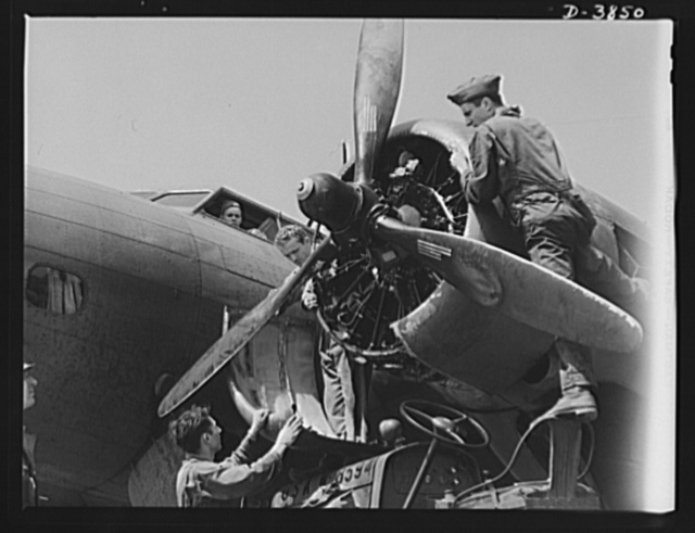 YB-17 bombardment squadron, Langley Field, Virginia. There isn't much these sodlier-mechanics don't know about big airplane engines. Non-coms of a bombardment squadron at Langley Field, Virginia install a ring cowling around one of the four powerful engines of a YB-17 bomber