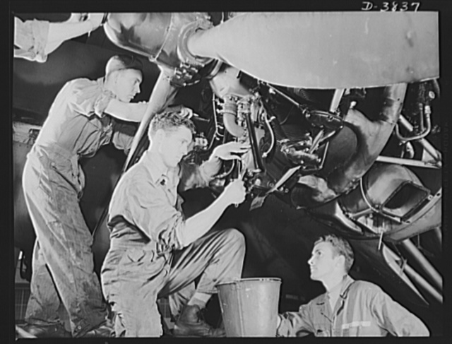 YB-17 bombardment squadron, Langley Field, Virginia. Tuning a bomber engine requires knowledge and skill. These three corporals of a bombardment squadron at Langley Field, Virginia are making adjustments that will put a mighty YB-17 bomber in the pink of condition