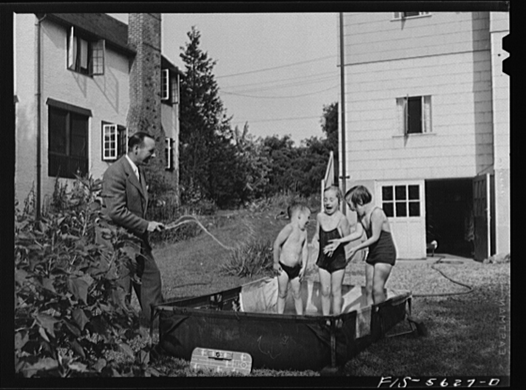 Yonkers, New York. Mr. Garrity building a wading pool in the backyard for his children