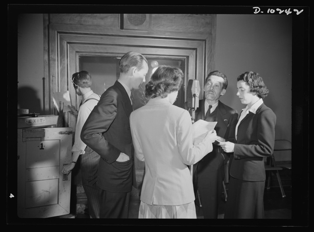 """""""You Can't Do Business With Hitler."""" Rehearsal is underway for the radio show """"You Can't Do Business With Hitler"""" written and produced by the radio section of the Office of War Information (OWI). At the microphone are (left to right) Sam Lauder, Marian Harvey (with back turned), Robert Pollard and Ilona Killian"""