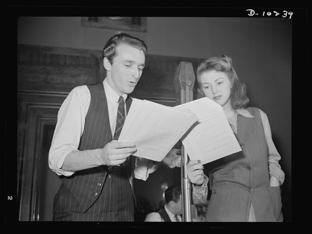 """""""You Can't Do Business With Hitler."""" Rehearsing for the radio show """"You Can't Do Business With Hitler"""" are John Flynn and Virginia Moore. This series of programs, broadcast at least once weekly by more than 790 radio stations in America, is written and produced by the radio section of the Office of War Information (OWI)"""