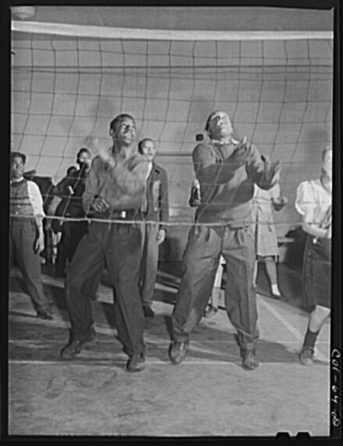 """Young """"Wellstowners"""" playing volleyball in the recreation hall at the community center of the Ida B. Wells Housing Project, Chicago, Illinois"""