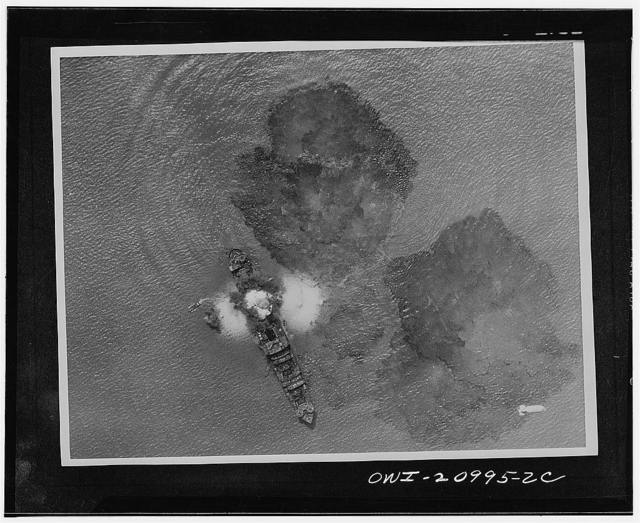 A 7,000 ton Japanese merchant vessel after a direct hit by India Air Task forces near Rangoon, India. A bomb is dropping in the lower right part of the picture and small boats are trying to carry the crew members away from the sinking vessel. The waters are covered with oil slick