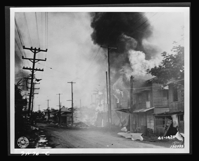 A burning building along Taft Avenue which was hit during the Japanese air raid in Barrio, Paranque, December 13, 1941, the Philippine Islands