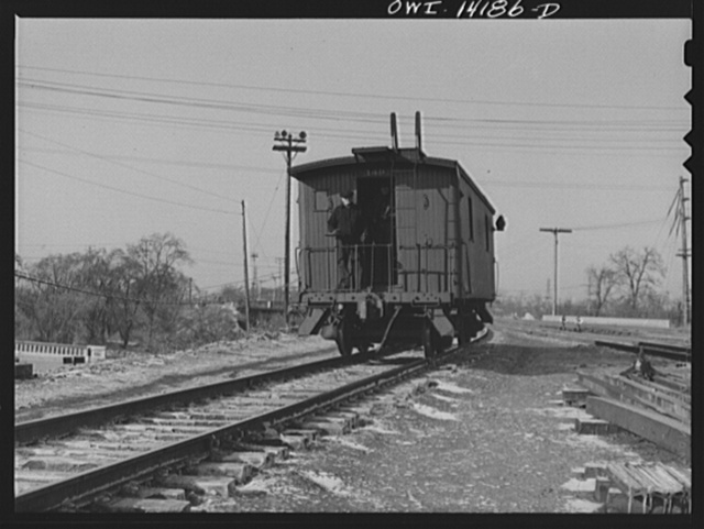 A caboose rolling down the hump to join its train in a classification yard of the Indiana Harbor Belt Railroad