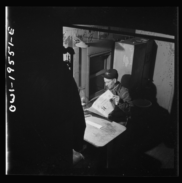 A conductor studying a timetable in the caboose on the Atchison, Topeka and Santa Fe Railroad between Chillicothe, Illinois and Fort Madison, Iowa