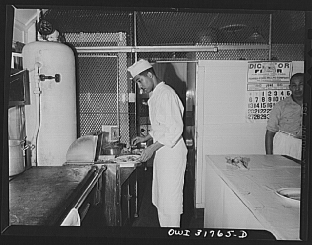A cook preparing plates in the kitchen of the towboat Ernest T. Weir going down the Ohio River to Cincinnati