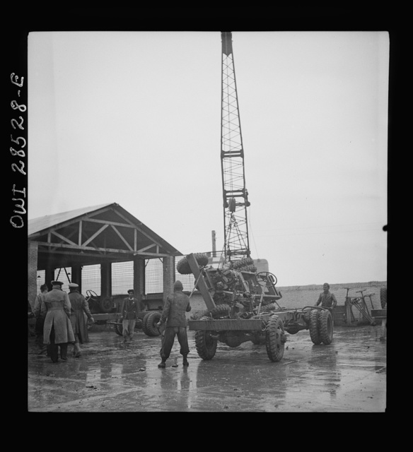 A derrick moving a chassis as the men work ankle deep in water at an American truck assembly plant somewhere in Iran