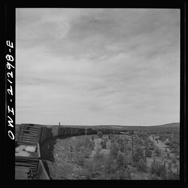 A diesel freight train on the Atchison, Topeka and Santa Fe Railroad between Winslow and Seligman, Arizona going down the mountains from Supai to Ash Fork, Arizona, a drop of about 1600 feet. A brakeman is riding on the top of the car. He stays on as far as Ash Fork, to operate the retainers