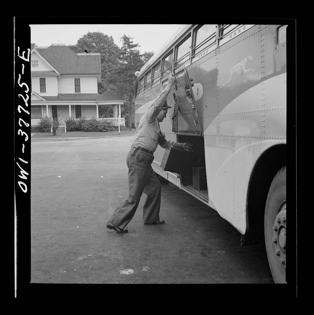 A Greyhound bus driver loading baggage at a small town between Chicago, Illinois and Cincinnati, Ohio