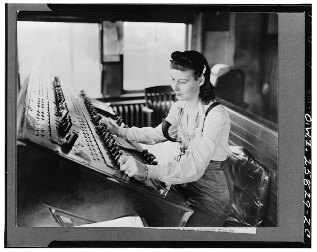 A switchtender on the Pennsylvania Railroad helping to classify freight trains at a large eastern freight yard. The electric controls on the board actuate rail switches in the yard. She is taking the place of a man now in the armed forces