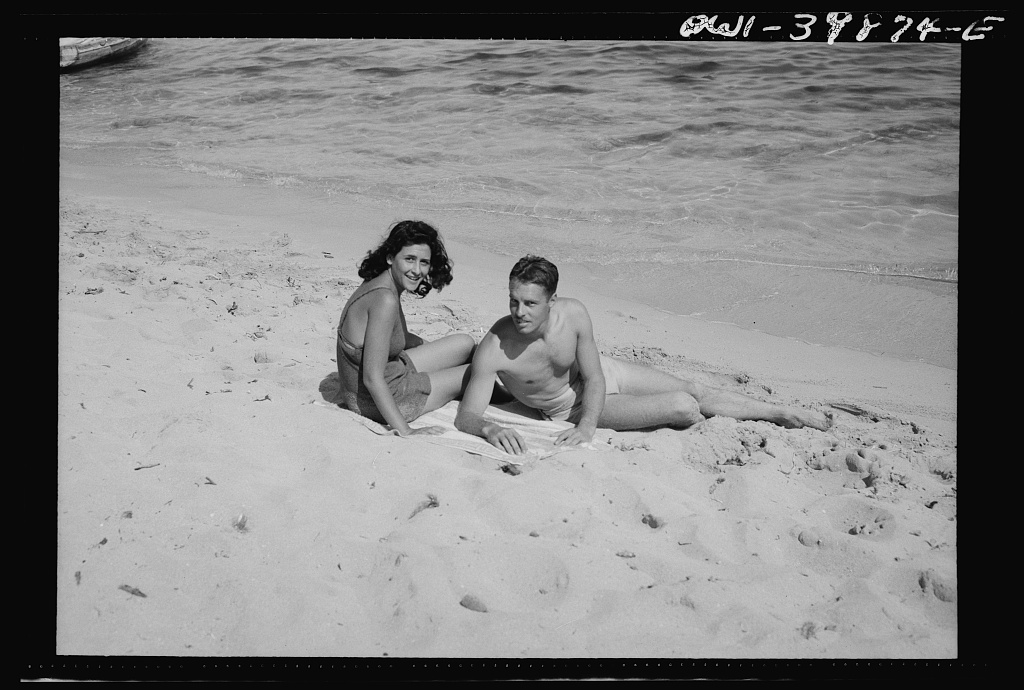A young couple on the beach in Sicily. The people are gradually returning to normal recreations