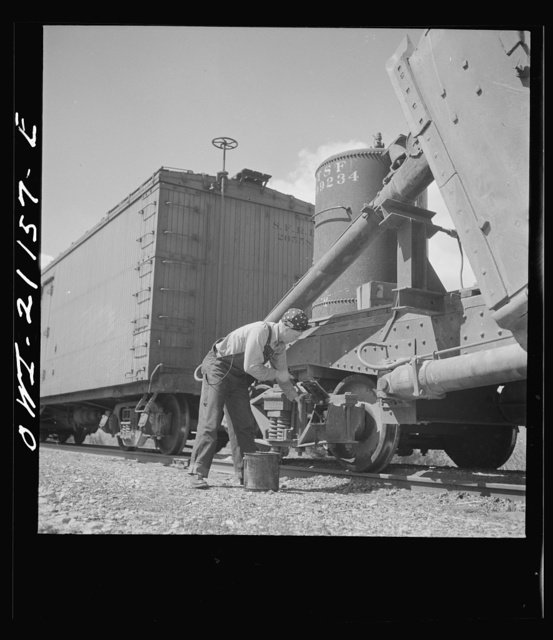 Acomita, New Mexico. Brakeman R.E. Capsey repacking a journal box of a special car as the train on the Atchison, Topeka and Santa Fe Railroad between Belen and Gallup, New Mexico waits on a siding