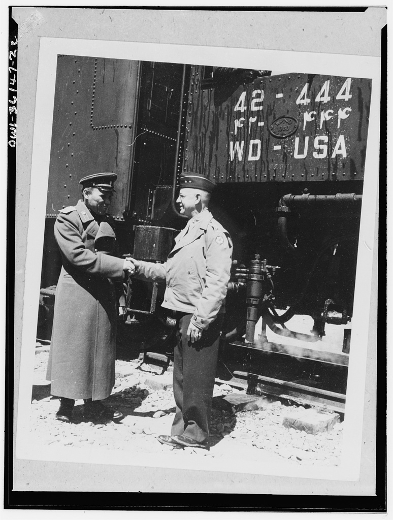 Against a background of an American locomotive inscribed with English and Persian numerals, Major-General Donald H. Connolly, Commanding Gerneral, Persian Gulf Service Command exchanging greetings with General A.M. Koroloff on the occasion of the arrival of the first All-American train from the Persian Gulf to the point where the freight load was turned over to the USSR (Union of Soviet Socialist Republics)