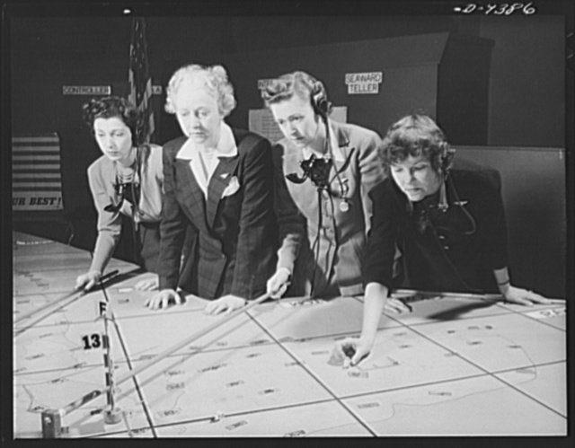 Aircraft warning service. Mrs. E.V. Rickenbacker (second from left) watches as a group of volunteer airplane plotters at a filter center push markers into place. Recruited by the Office of Civilian Defense, the volunteers work in shifts of four to five hours, often coming to the center after a day's work at the office. The plotters report every second or third day, contributing many hours to their work than involved in less exacting civilian defense operations