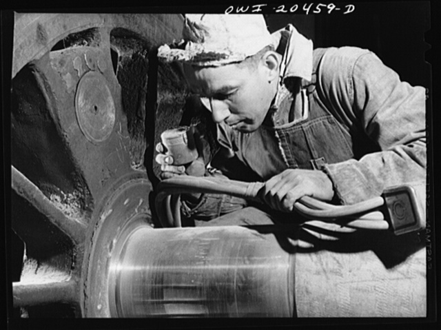 Albuquerque, New Mexico. Magnaflux inspector A.J. Fry at work on an engine wheel axle in the Atchison, Topeka and Santa Fe Railroad shop. The cable in his hand magnetizes the axle as he spreads steel dust over an area. He then cuts the current off and carefully blows the dust away. The steel particles remain, however in any tiny cracks and reveal any surface flaws that might exist. Axles of engine wheels are magnafluxed every 200,000 miles