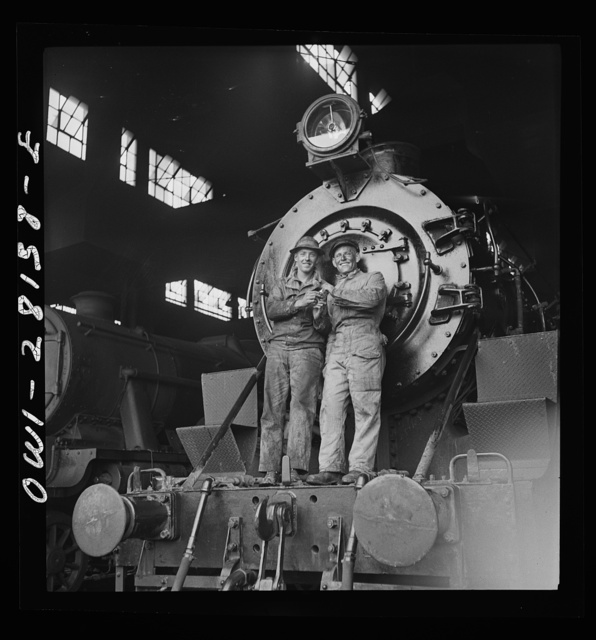 American and British engineers taking time out for a smoke. They are standing on an American engine somewhere in Iran