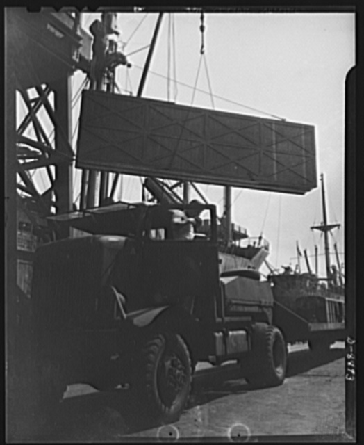 "American ""steam chickens"" arrive in Africa. From the ship which brought it to Africa, an American P-40 fighter plane is loaded onto a waiting American truck which will carry it to an airport for uncrating and assembly"