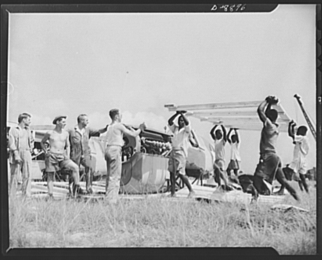 """American """"steam chickens"""" arrive in Africa. No time is lost at an African airport in uncrating the big package containing the P-40 fighter. An American foreman directs the unpacking of the plane's fuselage"""