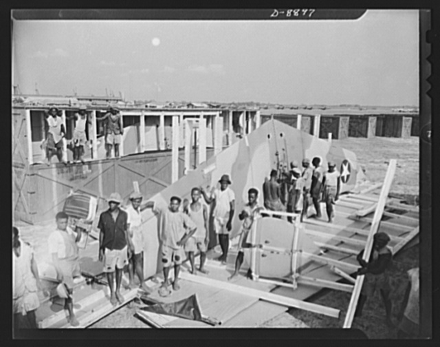 """American """"steam chickens"""" arrive in Africa. Some of the crew of natives employed by American forces to unload fighter planes at an African airport. These workmen have just uncrated a wing for a P-40"""