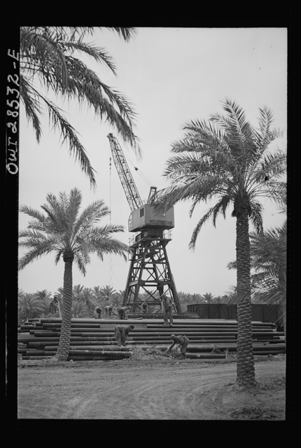 American troops unloading supplies for Russia with the aid of an American-made derrick somewhere in the Middle East