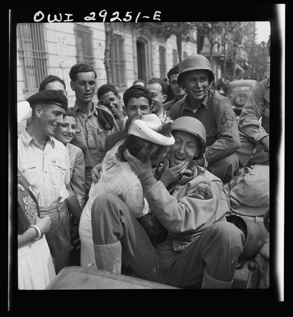 An American correspondent in an Army Jeep is welcomed with a kiss by a young lady in Porto Farina after the Allies frustrated the German evacuation attempts