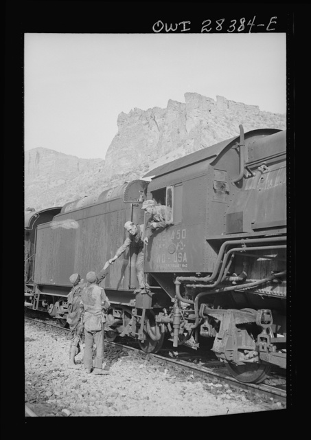 An American crew in the cab of an American engine are at a stop on the railway passing the time with some Iranian boys somewhere in Iran