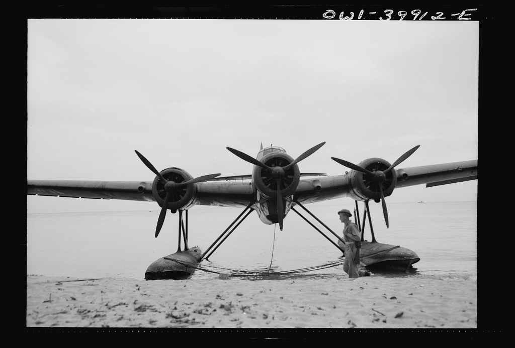 An Italian seaplane on a Sicilian beach guarded by a British soldier